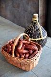 Cesta con las salchichas y la bombona de vino Imagen de archivo libre de regalías