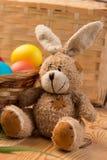 Cesta con los huevos coloreados y el conejito de pascua Imágenes de archivo libres de regalías