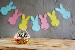 Cesta con los huevos de codornices y la guirnalda colorida de los conejitos en fondo de madera Imagen de archivo