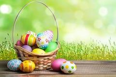 Cesta con los huevos de Pascua coloreados en el fondo del cielo fotos de archivo
