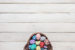 Cesta con los huevos de Pascua coloridos, pintados en hecho a mano en un viejo fondo de madera blanco Visión superior, estilo pla Foto de archivo