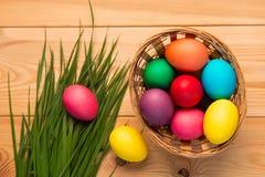 Cesta con los huevos de Pascua coloridos y la hierba enorme Imágenes de archivo libres de regalías