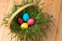 cesta con los huevos de Pascua con la hierba verde en un de madera Imágenes de archivo libres de regalías