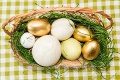 Cesta con los huevos de Pascua de oro Imágenes de archivo libres de regalías