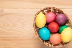cesta con los huevos de Pascua en una sobremesa de madera Imagen de archivo libre de regalías