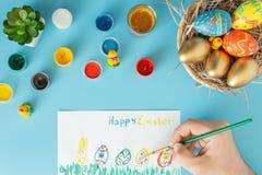 Cesta con los huevos de Pascua hechos a mano al lado de las pinturas y de la mano multicoloras con el cepillo que pintan los huev imagen de archivo libre de regalías