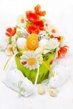 Cesta con los huevos de Pascua, las flores y los conejos blancos Imágenes de archivo libres de regalías