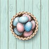 Cesta con los huevos de Pascua pintados en el fondo de madera azul, ejemplo libre illustration