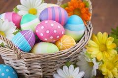 Cesta con los huevos de Pascua pintados a mano coloridos Imagen de archivo libre de regalías
