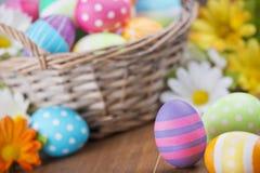 Cesta con los huevos de Pascua pintados a mano coloridos Imágenes de archivo libres de regalías
