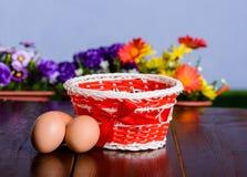 Cesta con los huevos en la tabla de madera rústica Imagen de archivo libre de regalías