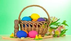 Cesta con los huevos, la joyería dulce y el alstroemeria imagen de archivo