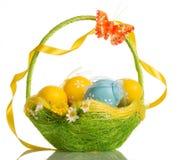 Cesta con los huevos, la mariposa y la cinta de Pascua en la manija, aislante imagen de archivo libre de regalías