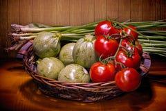 Cesta con los tomates, el calabacín redondo y las cebollas verdes Fotografía de archivo
