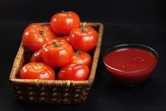 Cesta con solamente los tomates y la salsa de tomate intactos Imagenes de archivo