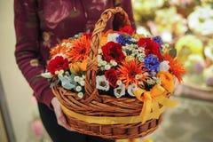 Cesta con un ramo de flores coloridas Imagen de archivo libre de regalías
