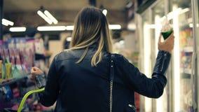 Cesta da loja da terra arrendada da mulher e gelado na mercearia ou no supermercado que têm o divertimento, músicas do canto usan vídeos de arquivo
