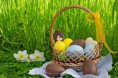 Cesta da Páscoa com os ovos de chocolate de easter e os ovos coloridos Fotografia de Stock Royalty Free