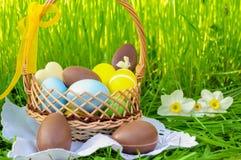 Cesta da Páscoa com os ovos de chocolate de easter e os ovos coloridos no gre Imagem de Stock