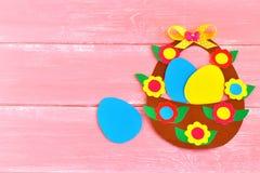 Cesta da Páscoa com os ovos e as flores feitos do cartão, no fundo de madeira cor-de-rosa, com espaço para felicitações à Páscoa Foto de Stock