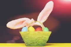 Cesta da Páscoa com ovos da páscoa coloridos e as orelhas de coelho peludos Fotografia de Stock Royalty Free