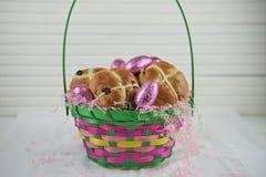 A cesta da Páscoa encheu-se com com os bolos transversais quentes frescos e os ovos cor-de-rosa brilhantes Imagem de Stock Royalty Free