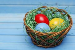 A cesta da Páscoa encheu-se com os ovos coloridos em um fundo de madeira azul imagem de stock royalty free