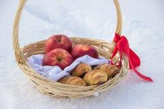 Cesta da palha com a fita do tampão vermelho com tortas e maçãs na neve Fotografia de Stock Royalty Free