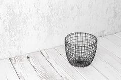 Cesta de alambre en el piso blanco Fotos de archivo