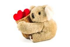 Cesta de bambu levando do urso de peluche completamente do coração Foto de Stock