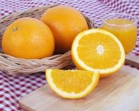 Cesta de completamente e meia laranja fresca na placa de madeira Fotografia de Stock Royalty Free