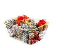 Cesta de compras con los regalos en el fondo blanco Imagenes de archivo