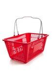 Cesta de compras plástica roja en un fondo blanco Imagen de archivo