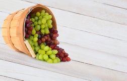 Cesta de derramamiento de las uvas en la tabla de madera Fotos de archivo libres de regalías