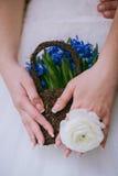 Cesta de flores azules, cierre del anillo y del control de la flor de la novia que lleva Imagenes de archivo