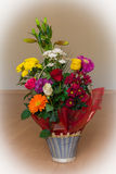 Cesta de flores coloridas em um assoalho de madeira fotos de stock