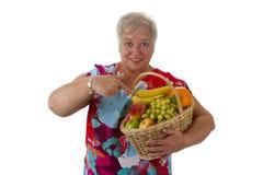 Cesta de fruta que se sostiene mayor femenina Imagen de archivo