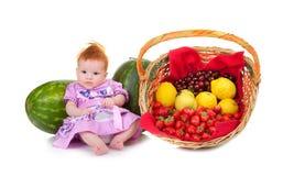 Cesta de fruta siguiente del bebé que se sienta lindo Imágenes de archivo libres de regalías