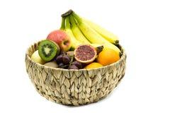 Cesta de fruto com as bananas, as maçãs, as laranjas e os quivis isolados no fundo branco fotografia de stock
