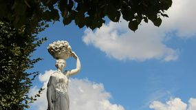 Cesta de frutos levando da moça da escultura do jardim em sua cabeça foto de stock