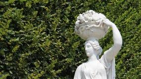Cesta de frutos levando da moça da escultura do jardim em sua cabeça imagem de stock