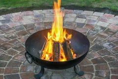 Cesta de fuego forjada con el fuego que se calienta en círculo de piedra hermoso de pavimentación en el jardín imagen de archivo