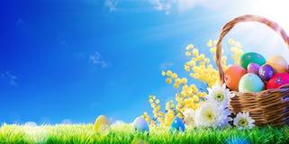 Cesta de huevos de Pascua pintados a mano con la mimosa en hierba fotos de archivo