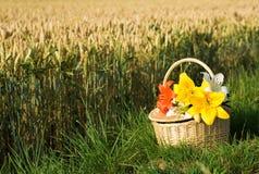 Cesta de la comida campestre con el manojo de flores Imagen de archivo libre de regalías