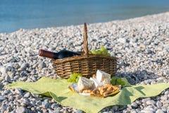 Cesta de la comida campestre con el vino, el queso y las uvas Fotografía de archivo