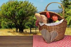 Cesta de la comida campestre con la comida y bebida en la tabla de madera Imágenes de archivo libres de regalías