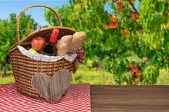 Cesta de la comida campestre con la comida y bebida en la tabla de madera Imagenes de archivo