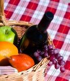 Cesta de la comida campestre con las frutas y el vino Imagen de archivo