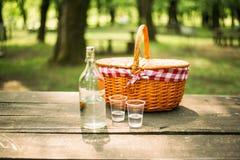Cesta de la comida campestre en una tabla en el bosque Fotos de archivo