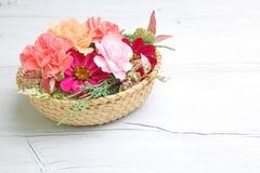 Cesta de la flor en un fondo de madera Imagen de archivo libre de regalías